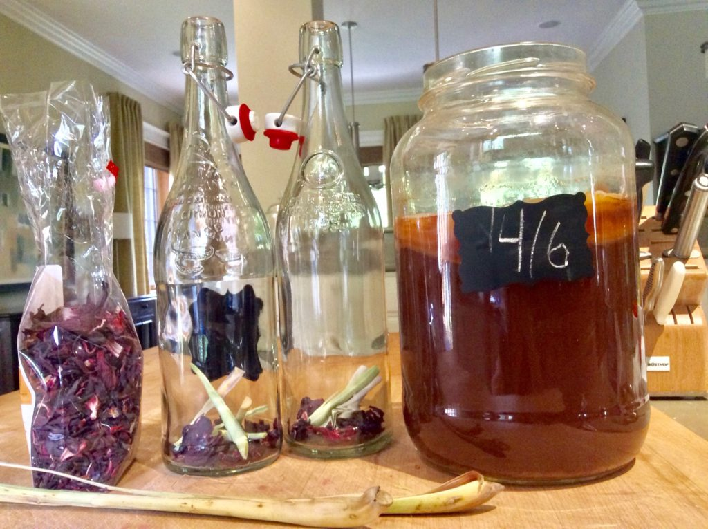 Ingredients to make hibiscus Kombucha along with two flip top bottoms and a large clear jar