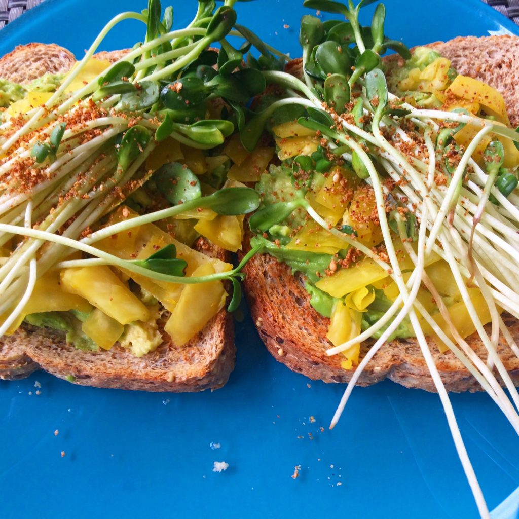 Avocado toast with curry sauerkraut, sprouts and gomasio